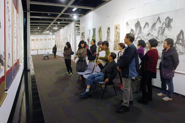 金嘉倫老師坐在椅子上,詳細講解他的書畫作品。在旁觀眾耐心聆聽教導。
